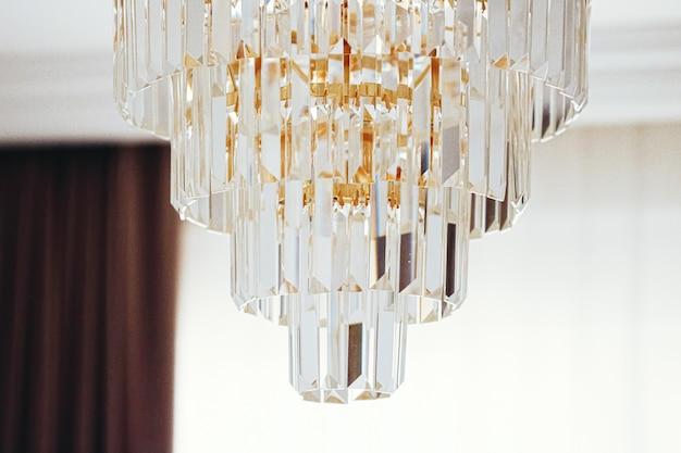 Lampadario in cristallo con dettagli dorati, mobili di lusso e concetto di arredamento per la casa