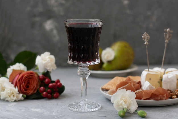 Bicchiere di cristallo con vino rosso al centro della cornice, accanto a un piatto con prosciutto e formaggio camembert e fiori