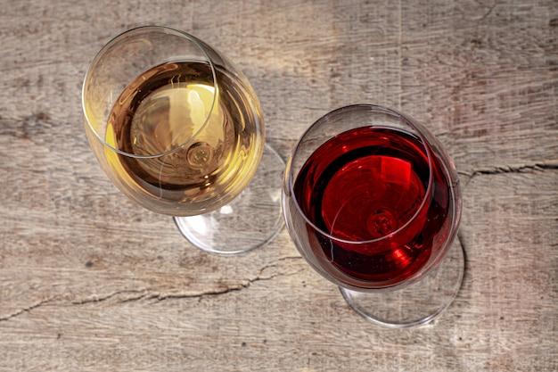 Bicchieri in cristallo con vino rosso e bianco su tavola in legno rustico