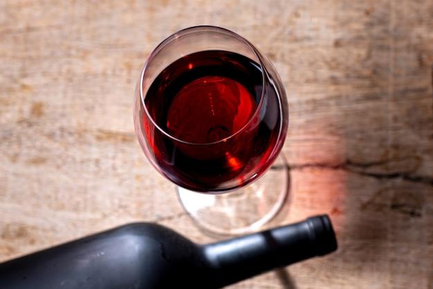 Calice di cristallo con vino rosso e bottiglia sul tavolo in legno rustico