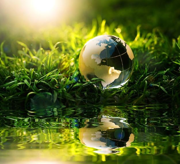 Crystal planet earth in riflessione sull'erba verde al tramonto