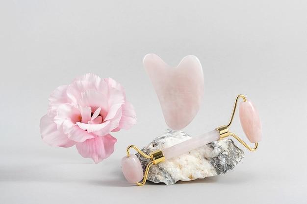 Rullo facciale di cristallo di quarzo rosa e strumento di massaggio giada gua sha su pietre e fiore rosa naturale su sfondo grigio. massaggio viso antietà per un trattamento lifting e tonificante naturale a casa.