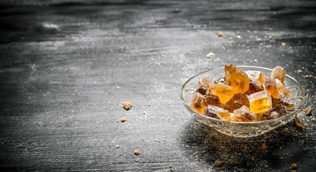 Zucchero di canna cristallino in un piattino. su sfondo nero rustico.