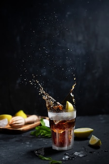 Cocktail ghiacciato cuba libre o long island con bevande forti, cola, limone e ghiaccio