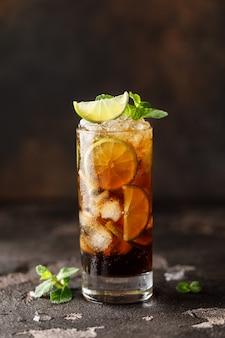 Cuba libre con rum marrone, cola, menta e lime. cocktail di tè freddo cuba libre o long island con bevande forti
