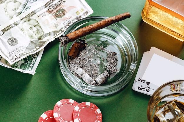 Sigaro cubano e soldi sulla superficie verde