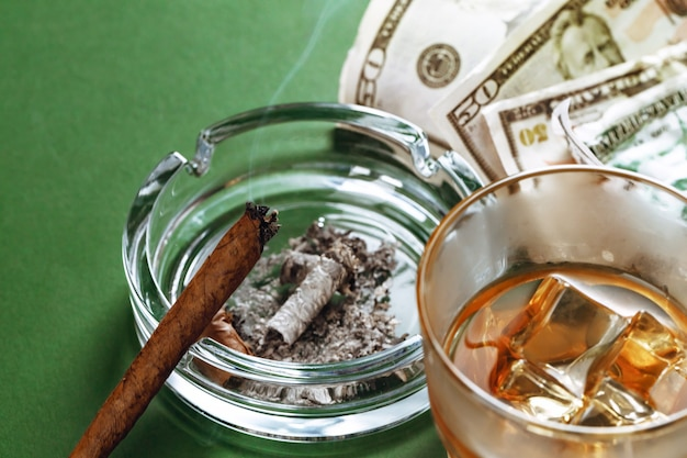 Sigaro cubano e denaro sulla superficie verde