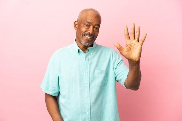 Anziano cubano isolato su sfondo rosa contando cinque con le dita