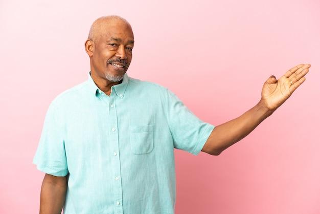 Anziano cubano isolato su sfondo rosa allungando le mani di lato per invitare a venire