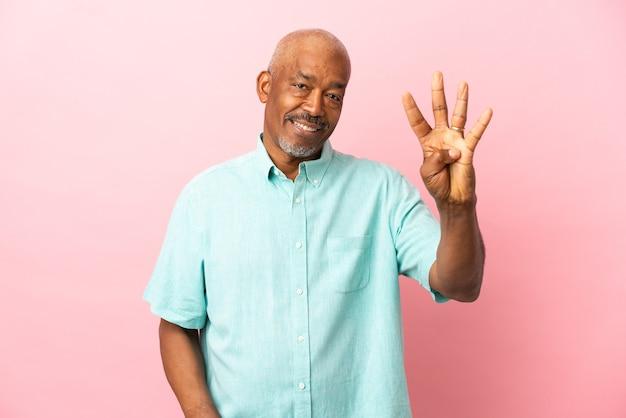 Anziano cubano isolato su sfondo rosa felice e contando quattro con le dita