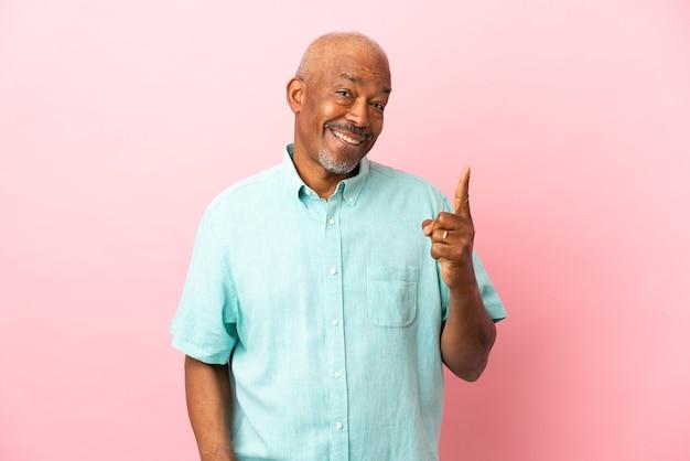 Anziano cubano isolato su sfondo rosa con l'intenzione di realizzare la soluzione sollevando un dito