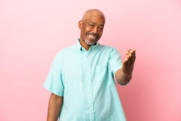 Anziano cubano isolato su sfondo rosa che stringe la mano per chiudere un buon affare