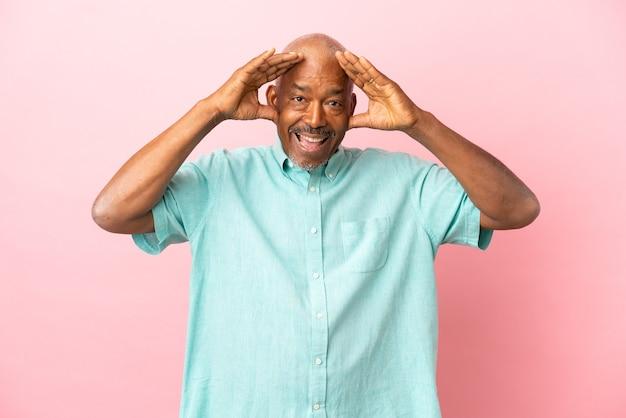 Anziano cubano isolato su sfondo rosa con espressione sorpresa