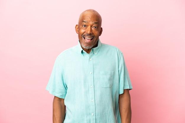 Anziano cubano isolato su sfondo rosa con espressione facciale a sorpresa
