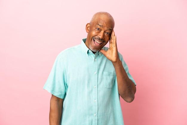 Anziano cubano isolato su sfondo rosa con espressione facciale sorpresa e scioccata