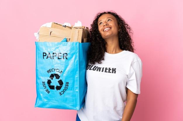 Donna cubana che tiene un sacchetto di riciclaggio pieno di carta da riciclare isolato sul colore rosa pensando un'idea mentre osservava