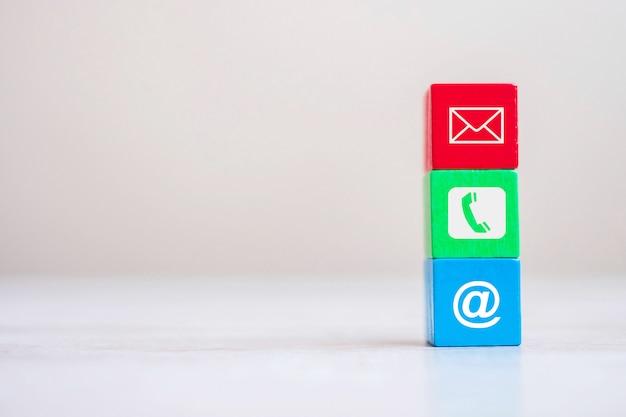 Cubo con il simbolo del sito web di posta elettronica, telefono e indirizzo sullo sfondo della tabella