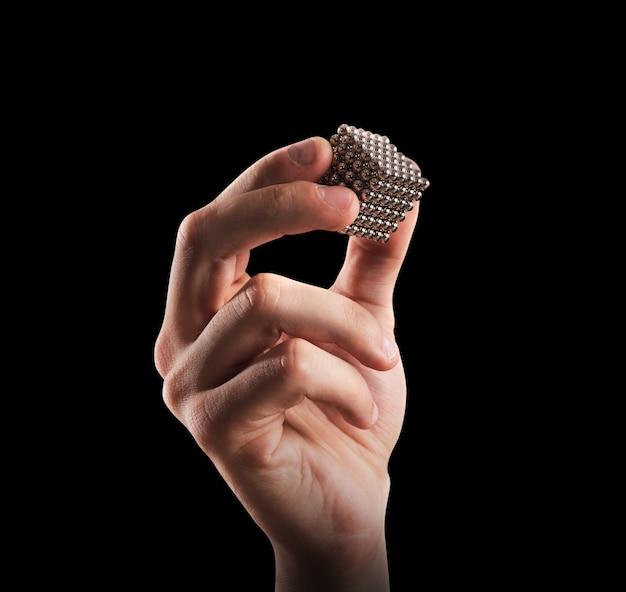 Cubo di sfere magnetiche tenuto da una mano. concetto di unione e partenariato