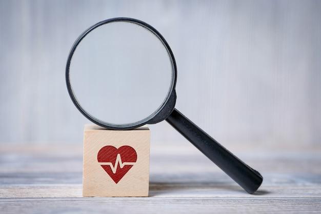 Cubo con cuore con icona cardiogramma e lente d'ingrandimento. concetto di ricerca di informazioni mediche.