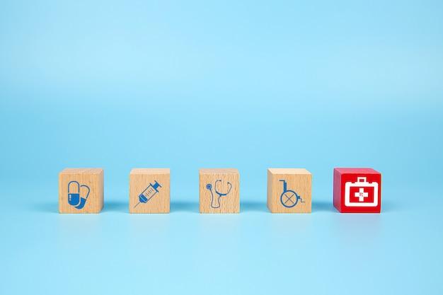 Cubo di blocchi di legno del giocattolo con l'icona del bambino medico e di primo soccorso.