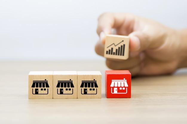 Blog cubo di giocattoli in legno con icona del negozio di marketing in franchising e mano che sceglie l'icona del grafico dietro.
