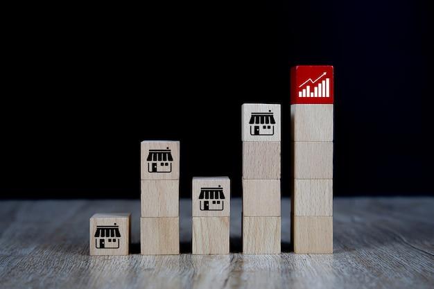 Blog cubo di giocattoli in legno con icona del negozio di marketing in franchising e icona del grafico.