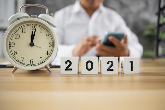 Cubo dell'anno numero 2021 sulla tavola di legno con uomo d'affari utilizzando il telefono che lavora online