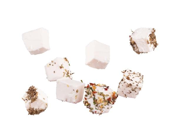 Cubetti di feta alle spezie su sfondo bianco