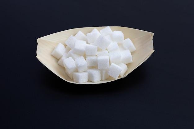 Cubetti di zucchero sulla superficie scura. copia spazio