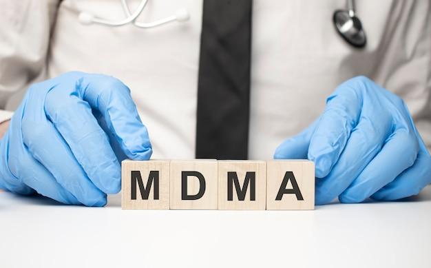 Cubi con la parola mdma sulla mano del medico. concetto di cura.