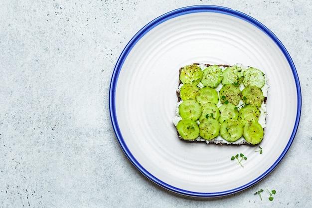 Toast di cetriolo e crema di formaggio sulla piastra bianca, vista dall'alto. concetto di dieta vegetariana sana.