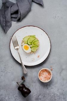 Panini al cetriolo, uova e ricotta su sfondo grigio cemento. vista dall'alto.