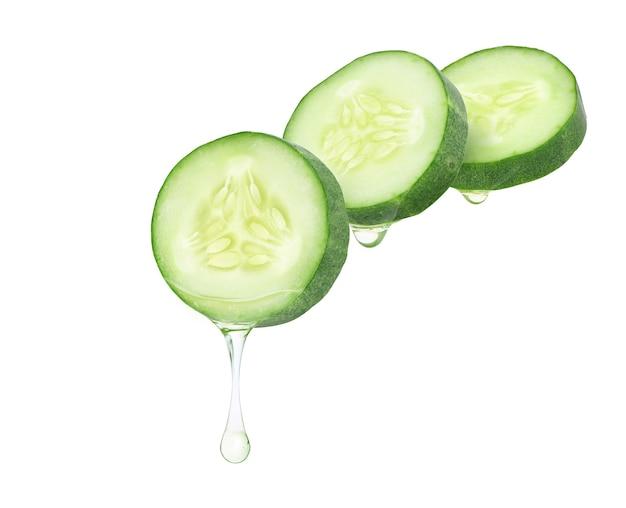 Olio essenziale di cetriolo che gocciola dalle fette di cetriolo isolate su sfondo bianco.