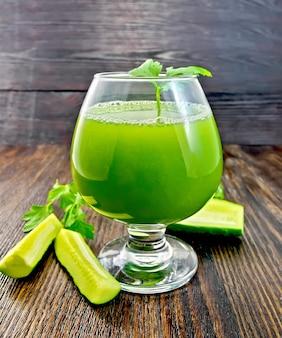 Succo di cetriolo in un bicchiere di vino, fette di cetriolo e prezzemolo su uno sfondo di tavola di legno