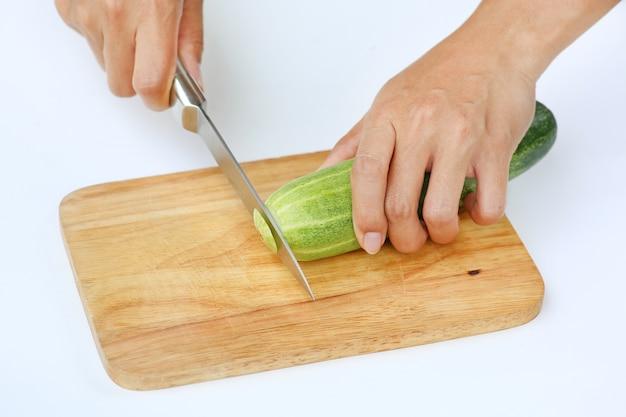 Fette del cetriolo sul blocco di legno con il coltello contro fondo bianco