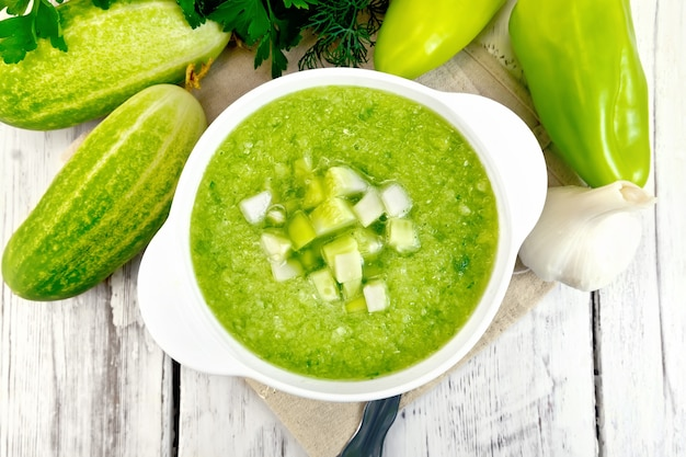 Zuppa di cetrioli con peperoni verdi e aglio in una ciotola su un tovagliolo, prezzemolo su uno sfondo di assi di legno sopra
