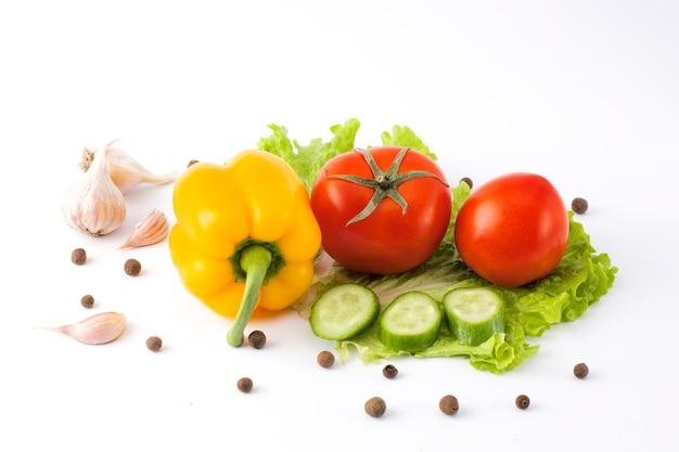 Cetriolo con pomodoro e pepe su uno sfondo bianco. verdure su uno sfondo bianco. verdure fresche multicolori su uno sfondo bianco.