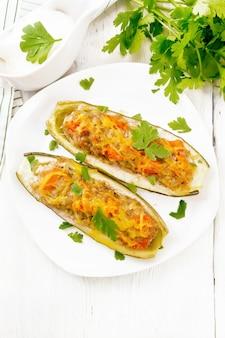 Cetrioli ripieni di carne macinata, pomodori, peperoni con formaggio e prezzemolo in piastra, salsa di panna e verdure in una salsiera, un asciugamano su sfondo di tavola di legno dall'alto