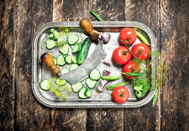 Cetrioli e pomodori alle erbe su un vassoio in acciaio. su una superficie di legno.