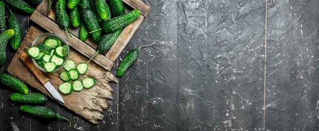 Cetrioli sul vassoio e fette di cetriolo su un tagliere con un coltello. su fondo rustico