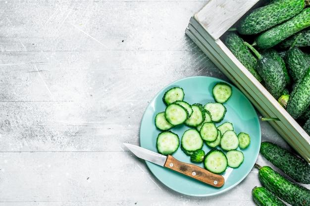 Cetrioli su un vassoio e fette di cetriolo su un piatto con un coltello.
