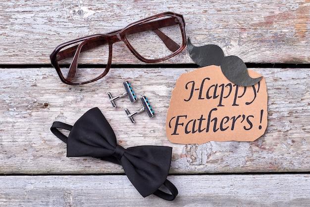 Gemelli, papillon e occhiali. biglietto di auguri con baffi. accessori alla moda per il padre.