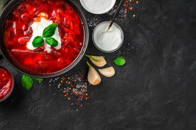 Sfondo culinario con zuppa di barbabietole, panna acida e basilico su uno sfondo di cemento nero. il concetto di piatti tradizionali.