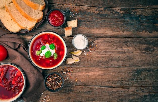 Sfondo culinario con spazio per copiare. zuppa di barbabietole con panna acida e basilico tra aglio, spezie e pane su uno sfondo di legno.