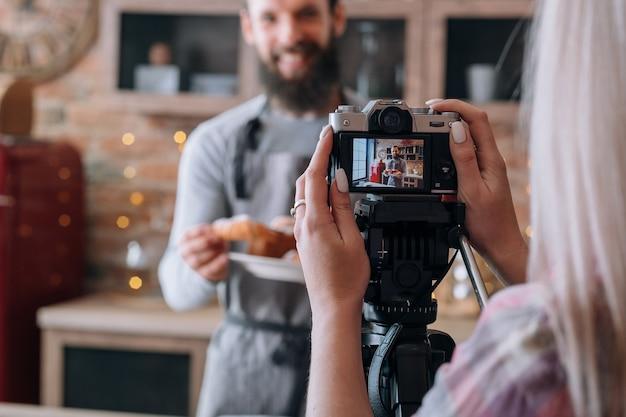 Blog culinario. hobby della cucina alimentare. video tutorial per riprese di coppia. uomo in grembiule. donna con macchina fotografica.