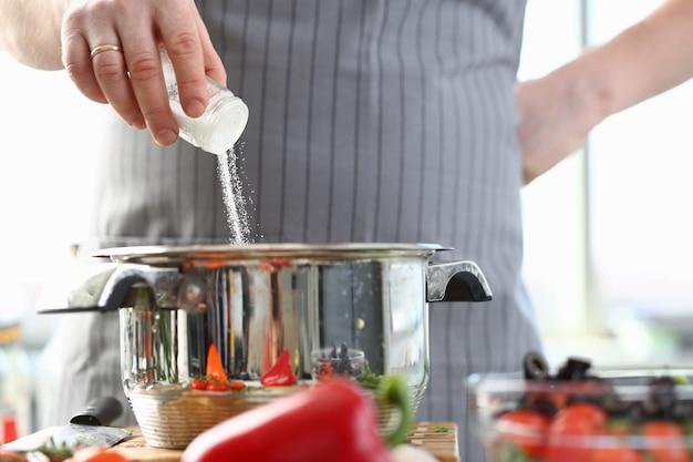 Chef culinario aggiunta di sale del mar bianco casseruola