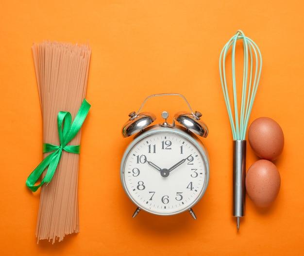 Concetto culinario, tempo di cottura con sveglia, pasta, uova di gallina, frusta