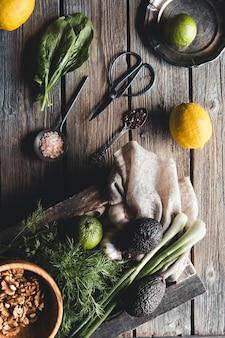 Erbe verdi culinarie, spinaci, aneto, prezzemolo, avocado in una scatola di legno isolata su sfondo bianco