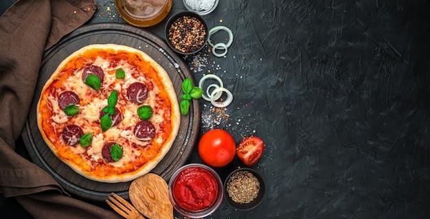 Panorama culinario con pizza con salame e formaggio e ingredienti su uno sfondo nero. il concetto di fast food.