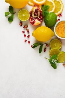 Parete culinaria per bevande rinfrescanti limonata, mojito o tè rinfrescante freddo. bouquet di limone fresco, lime, melograno, fiori di rosa tea essiccati, tè, zucchero di canna e foglie di menta